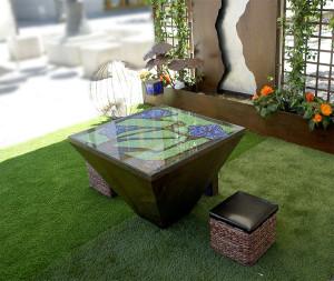 Mesa exterior construida en una bandeja de acero y decorada con cristales molidos de colores y cuentas de pulseras.