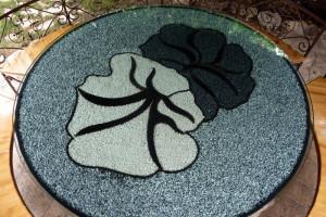 Mesa interior / exterior del pensamiento: Hecha de acero corten decorada con gravas de granito que dibujan la flor del pensamiento.